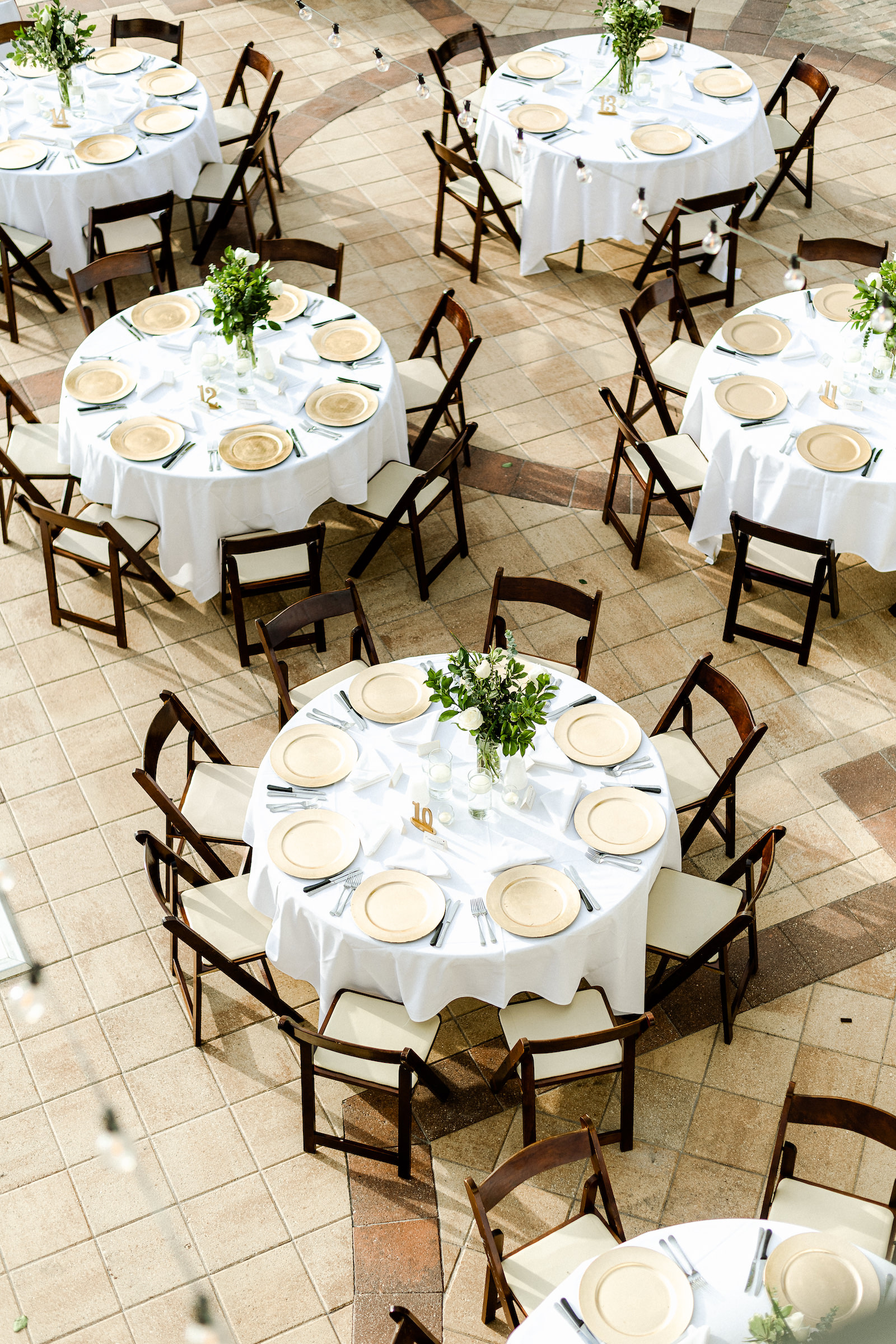 Outdoor wedding Reception with Round tables with white linens and mahogany wood folding chairs with gold charger plates and greenery centerpieces