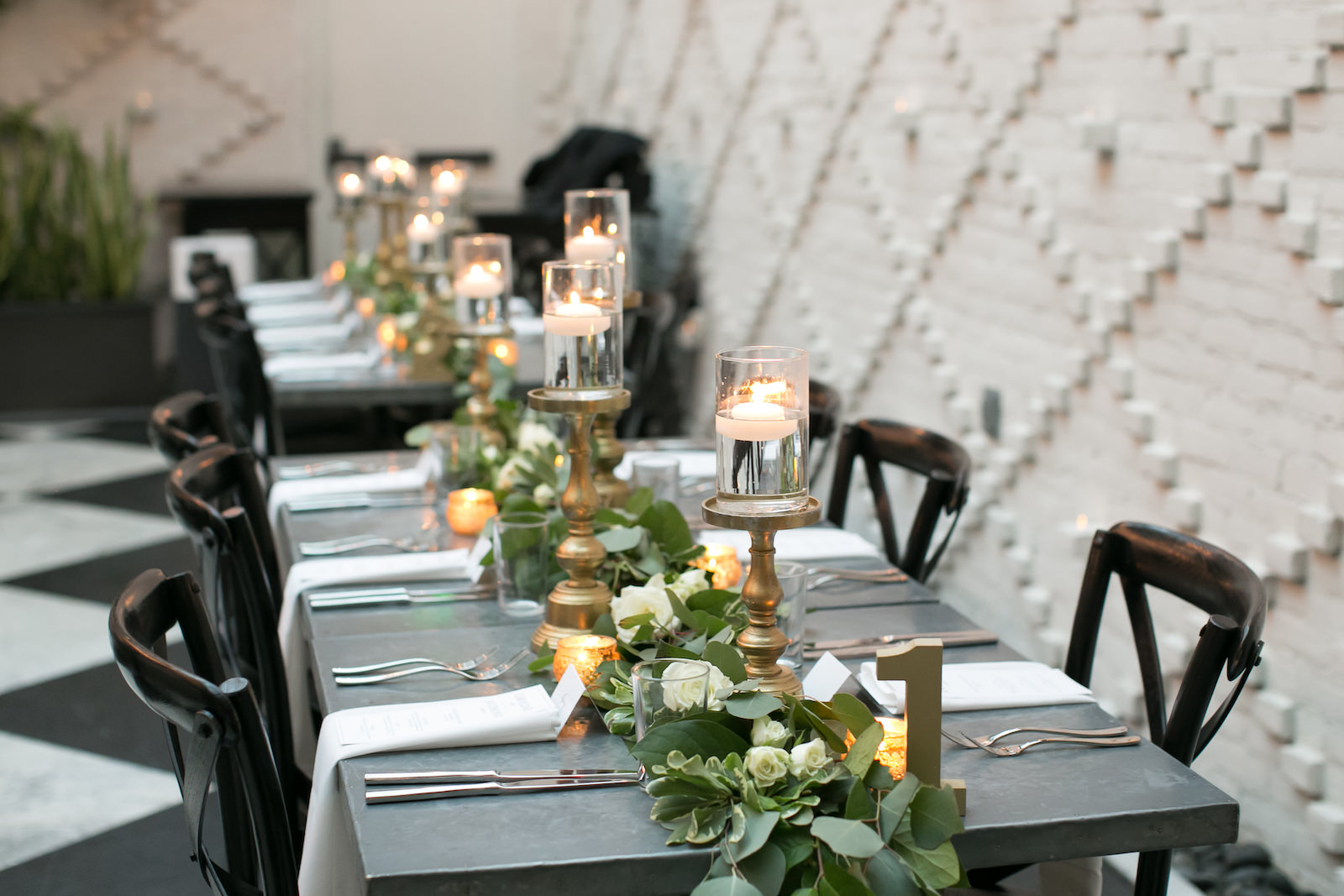Tampa Wedding Reception at Oxford Exchange Downtown Tampa | Long Metal Banquet Tables with Black Cross Back Chairs and White Napkins | Wedding Centerpieces of Floating Pedestal Candles and Greenery Garland