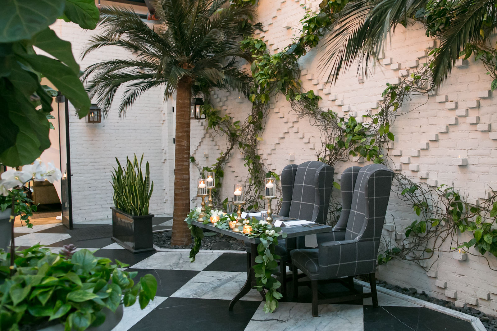 Tampa Wedding Reception at Oxford Exchange Downtown Tampa | Sweetheart Table with Upholstered Wingback Chairs and White Napkins | Wedding Centerpieces of Floating Pedestal Candles and Greenery Garland