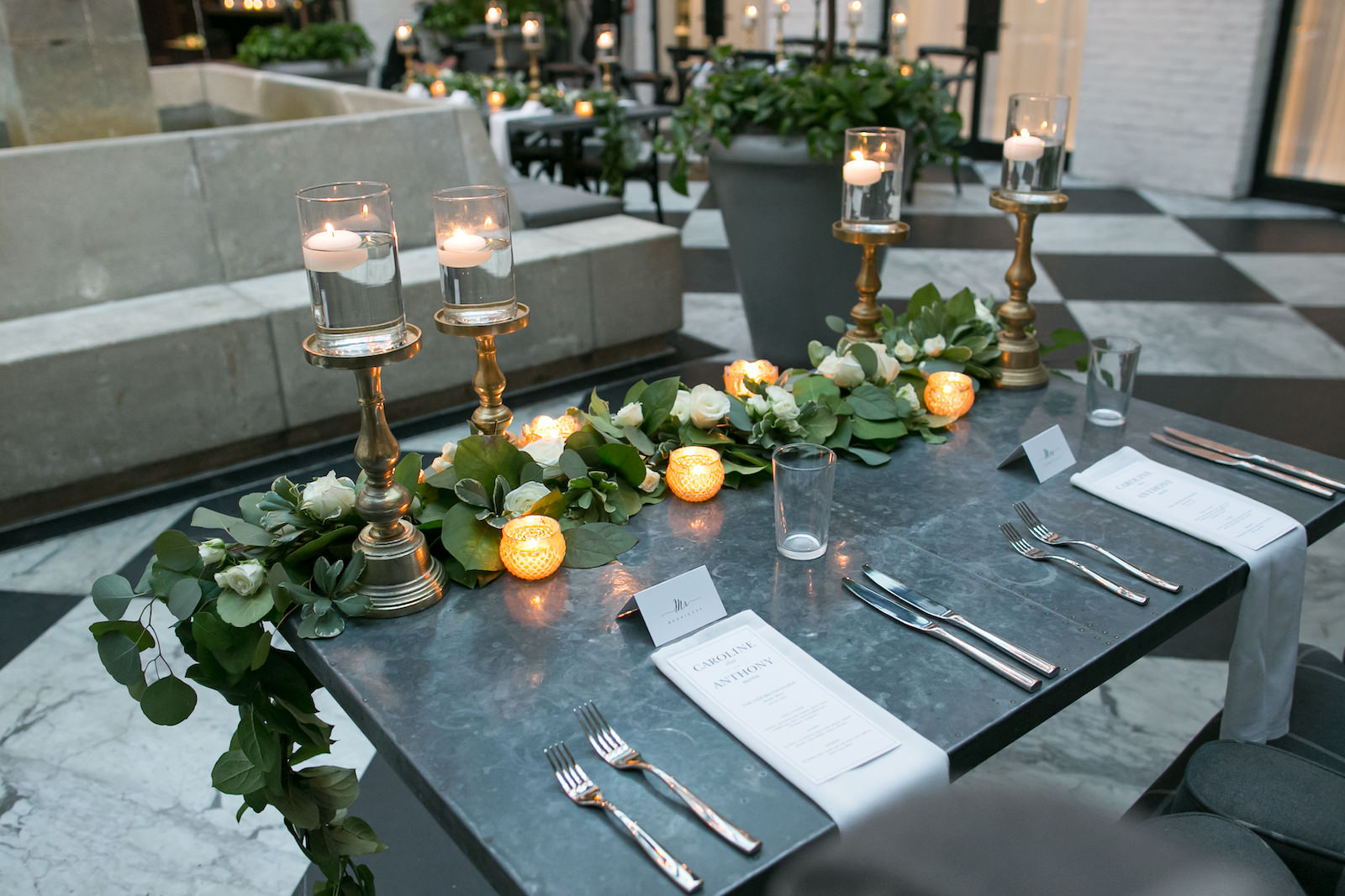 Tampa Wedding Reception at Oxford Exchange Downtown Tampa | Sweetheart Table with Upholstered Wingback Chairs and White Napkins with Menu Cards | Wedding Centerpieces of Floating Pedestal Candles and Greenery Garland