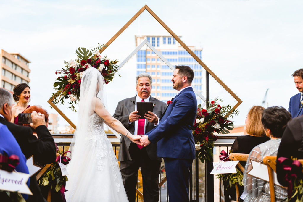 Bride and Groom Exchanging Wedding Vows During Rooftop Ceremony in Front of Geometric Sculpture | Tampa Bay Wedding Planner Special Moments Event Planning | Downtown St. Pete Wedding Venue Red Mesa Events