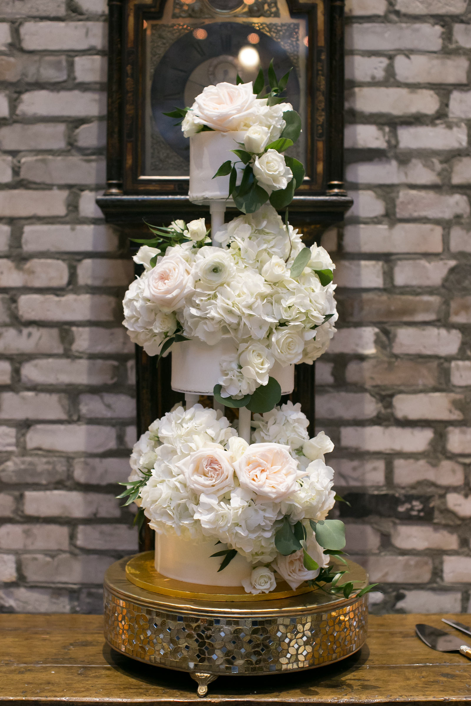 Three Tier Wedding Cake Filled with White Hydrangea and Roses on Gold Round Mosaic Cake Stand