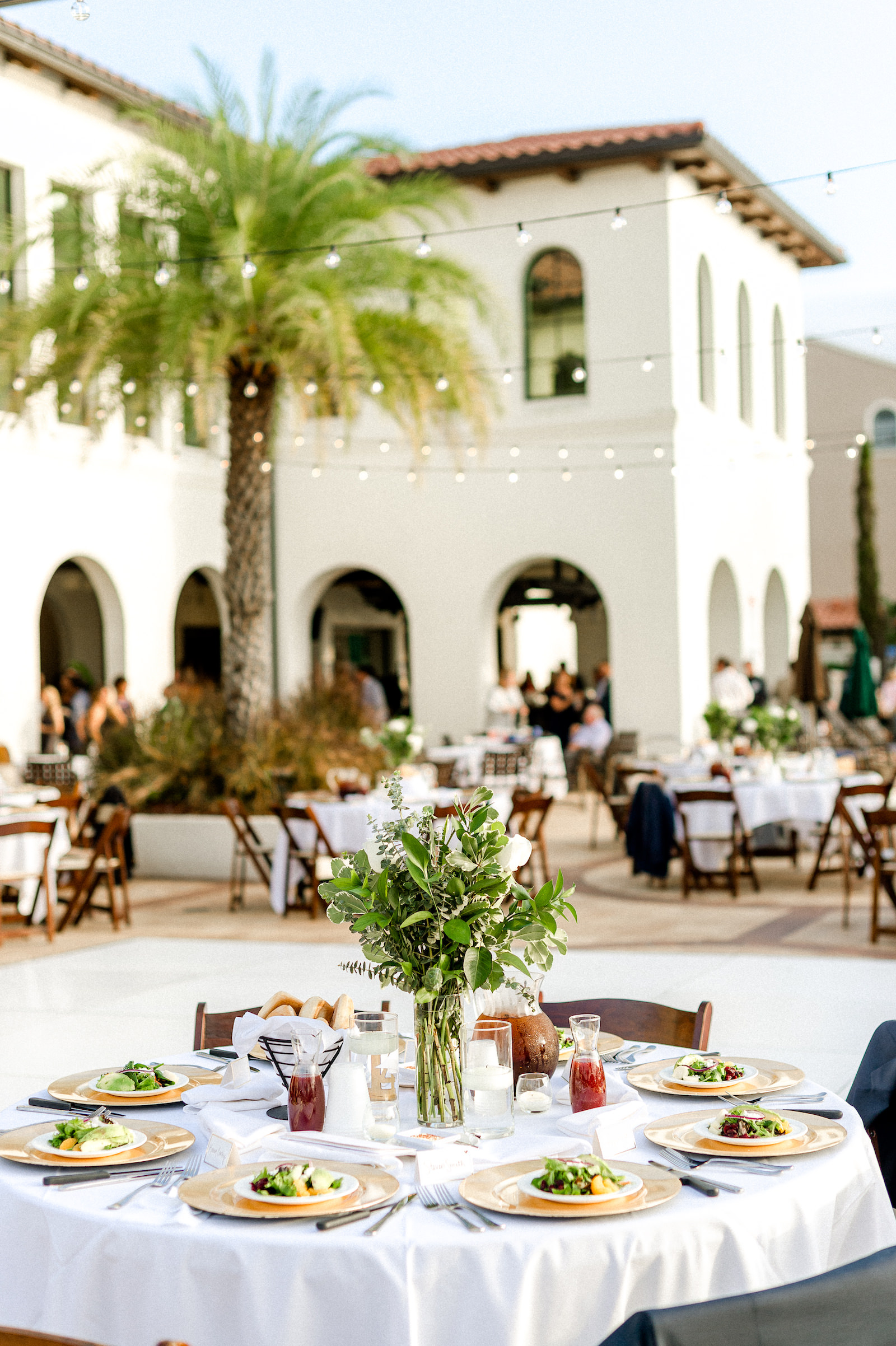 Outdoor wedding Reception at Tampa wedding Venue Westshore Yacht Club | Round tables with white linens and mahogany wood folding chairs with gold charger plates and greenery centerpieces