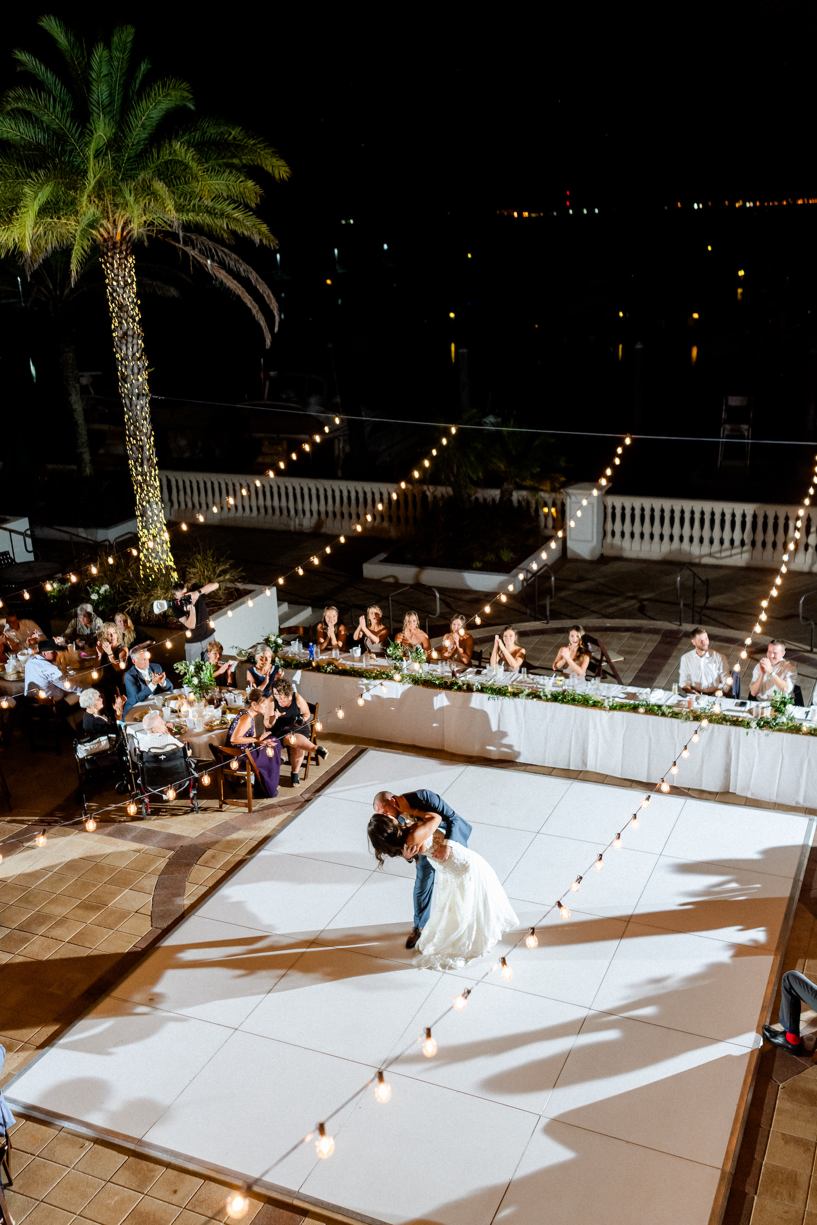 Bride and Groom First Dance on white Dance Floor under Canopy String Lights | Outdoor wedding Reception at Tampa wedding Venue Westshore Yacht Club | Long head table with greenery garland centerpieces