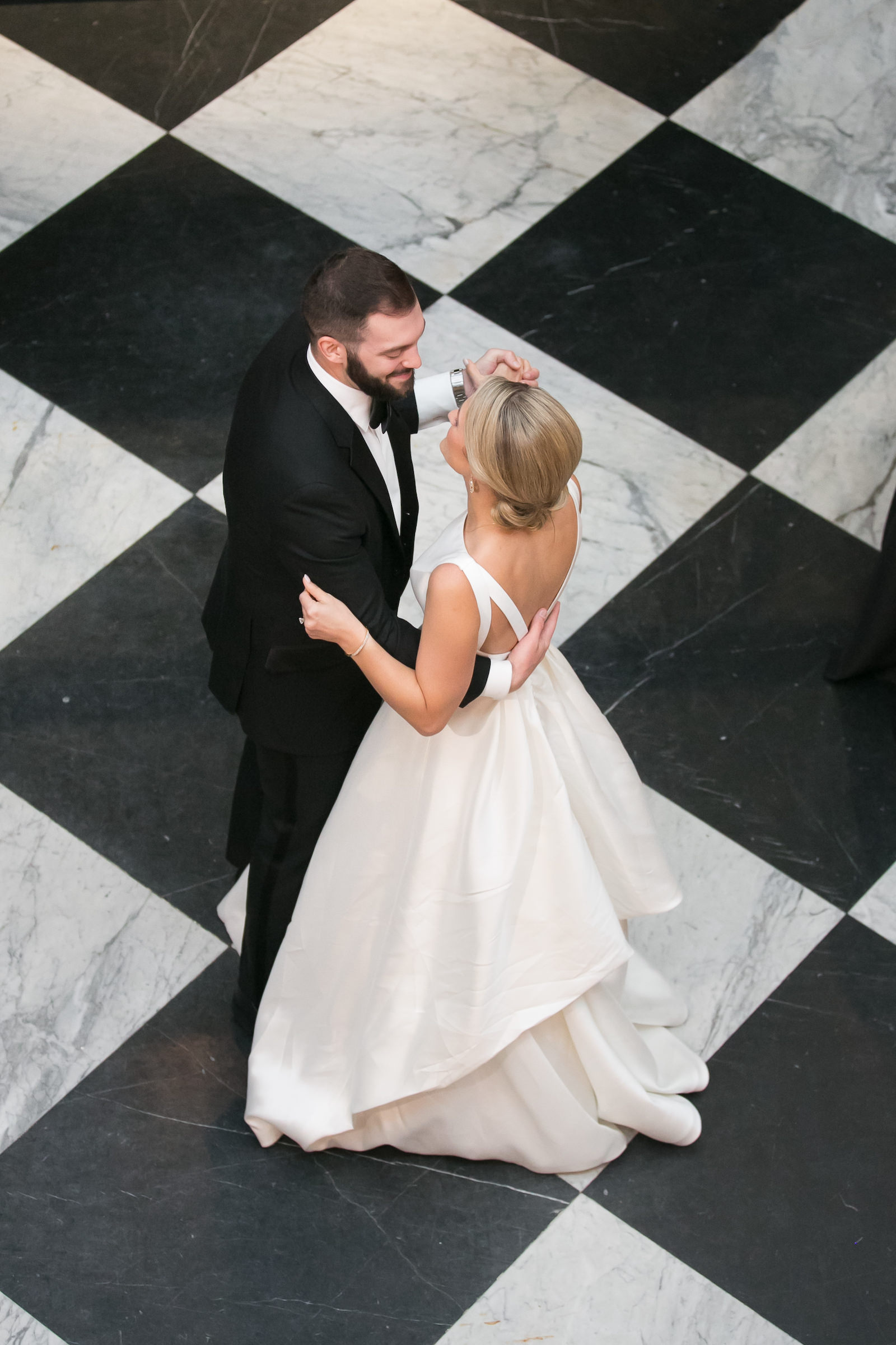 Bride and Groom First Dance at Oxford Exchange Wedding Reception in Downtown Tampa | Bateau Neck Mikado Satin Martina Liana Simple Elegant Wedding Dress with Buttons Down Back | Groom in Classic Black Tux