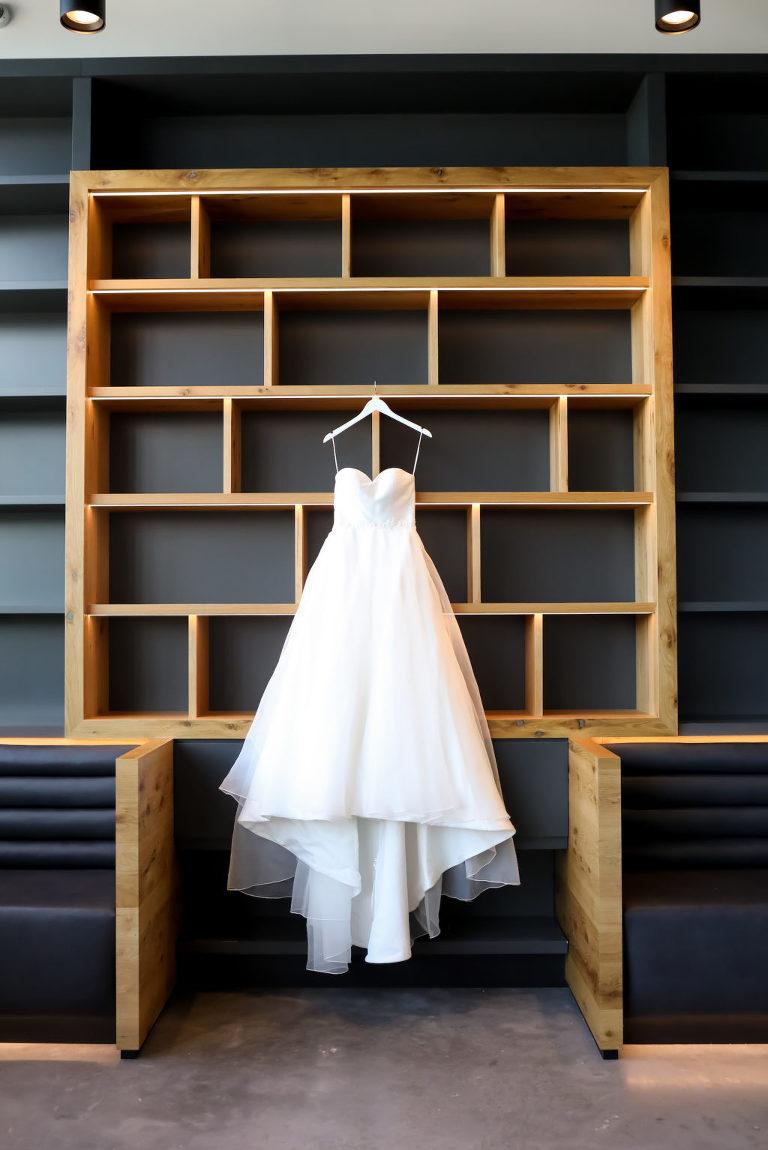 Wedding Dress Hanger Shot on Modern Bookshelf Wall at Tampa Wedding Venue Hyde House | Sincerity Bridal Designer Wedding Dress Bridal Gown with Sweetheart Neckline