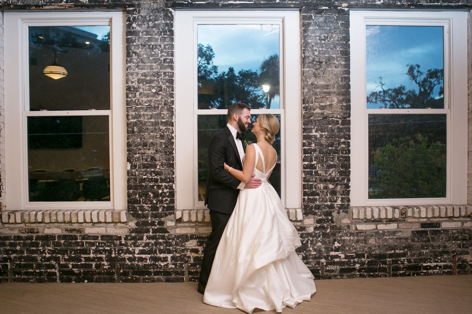 Bride and Groom Indoor Portrait with Exposed Brick Wall Backdrop at Oxford Exchange Wedding Reception in Downtown Tampa | Bateau Neck Mikado Satin Martina Liana Simple Elegant Wedding Dress with Buttons Down Back | Groom in Classic Black Tux