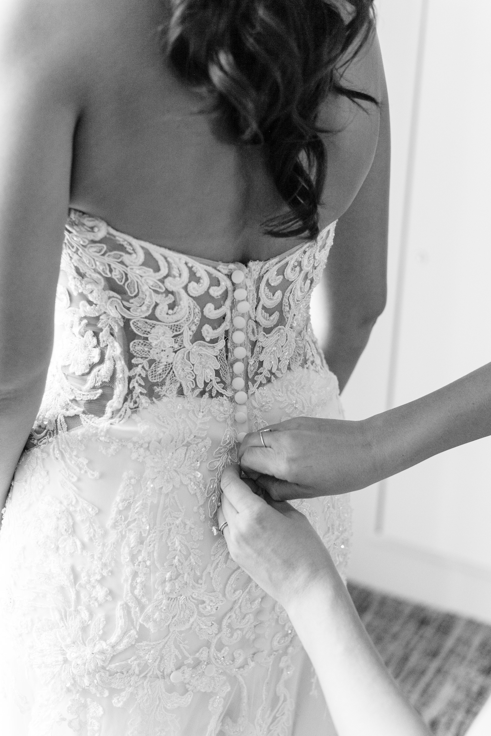 Black and white wedding Photography | Bride Getting Dressed with Sheer Illusion Lace Back Wedding Dress and Buttons | Dewitt for Love Photography