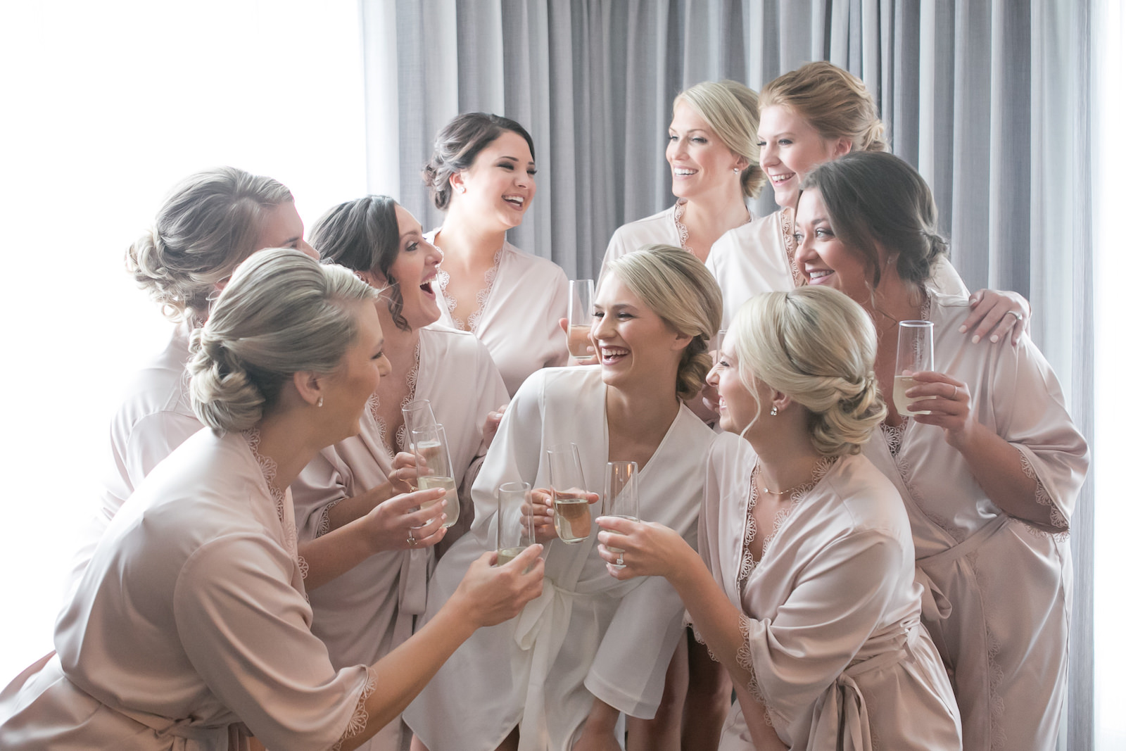 Bride and Bridesmaids Getting Ready in Taupe Robes with Bubbly Champagne | Carrie Wildes Photography