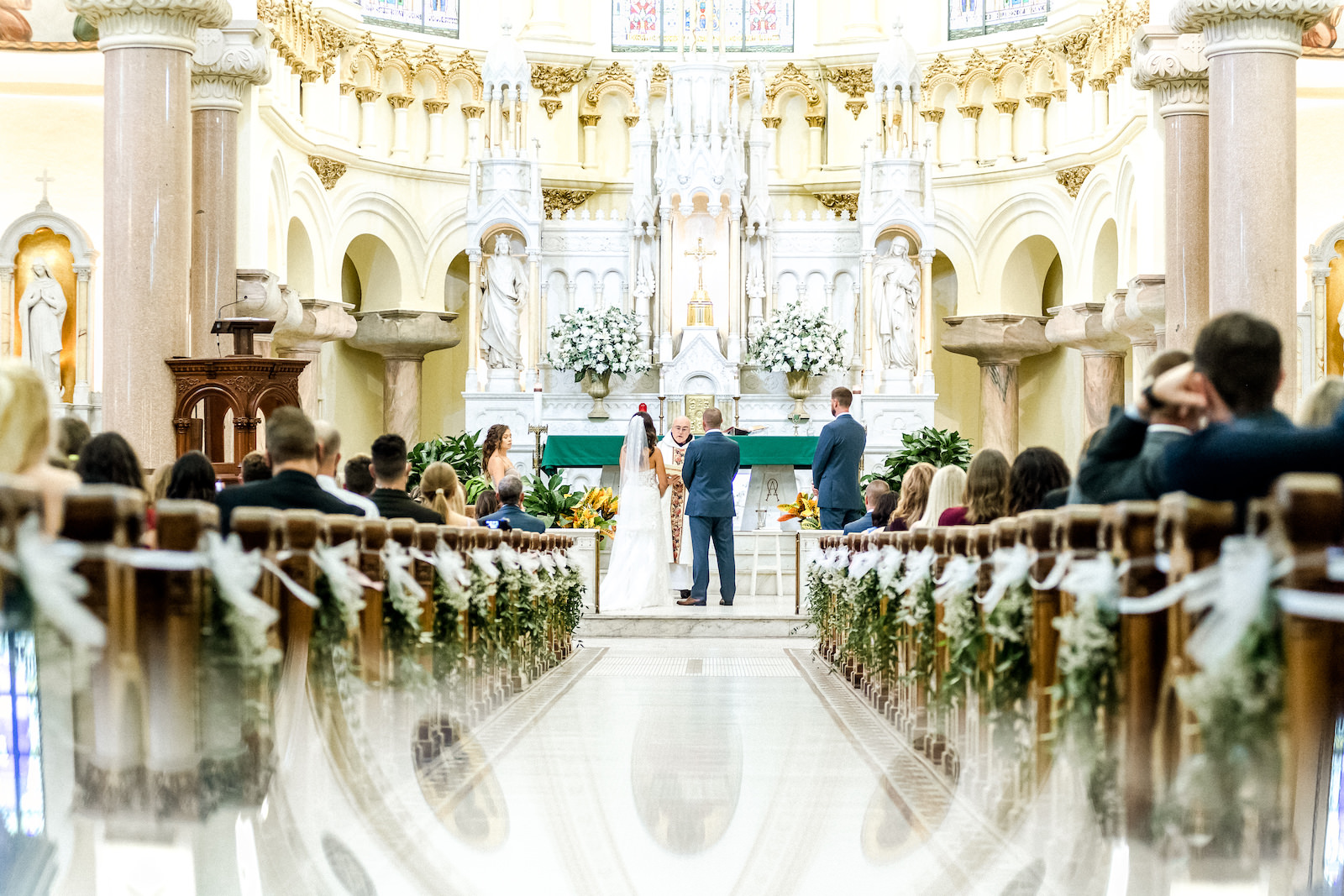 Bride and Groom Exchanging Vows during Downtown Tampa Wedding Ceremony at Sacred Heart Catholic Church | Church Ceremony Aisle with Greenery | Groom Wearing Classic Navy Suit | Dewitt for Love Photography