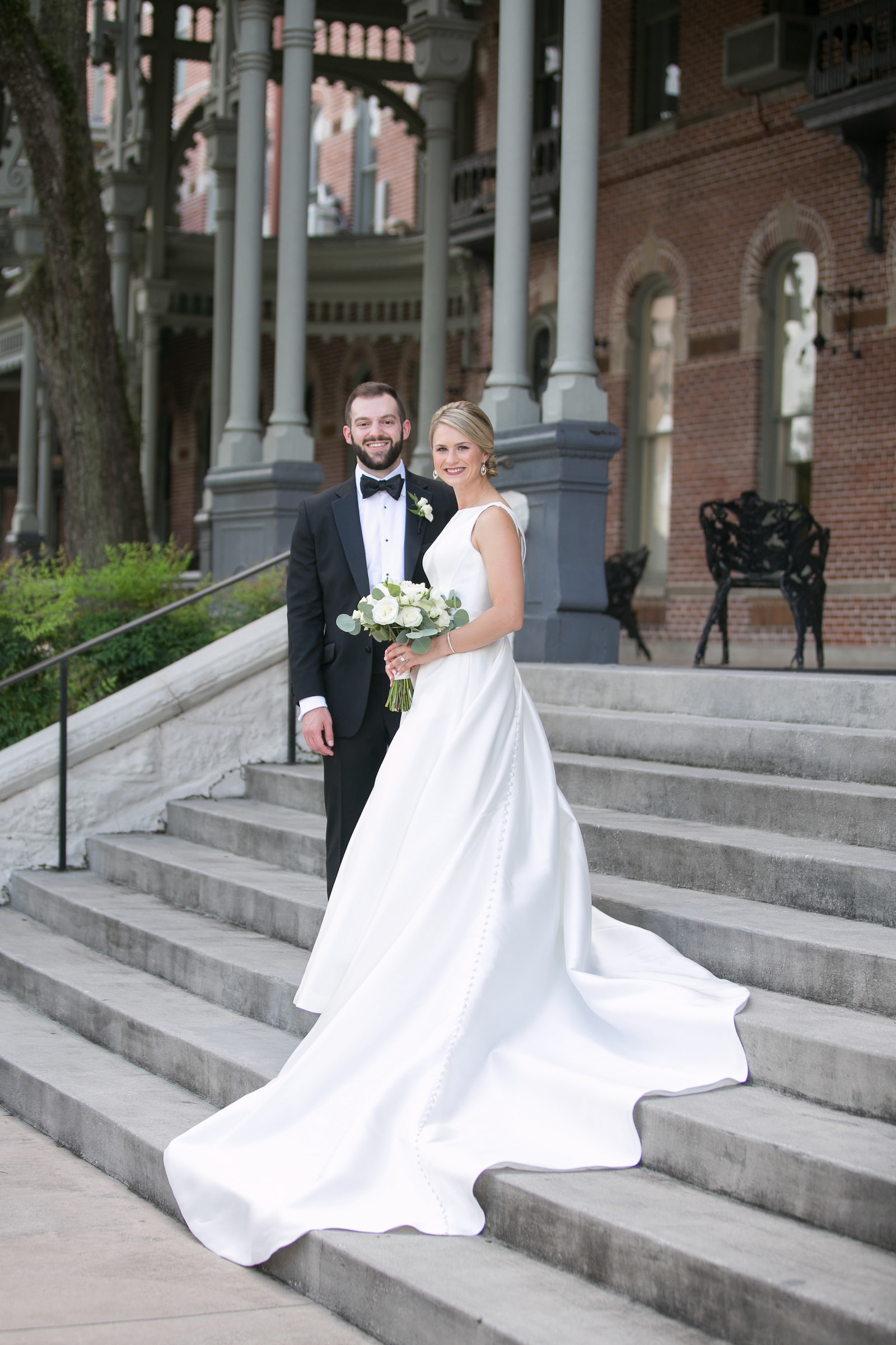 Bride and Groom Outdoor Portrait in Downtown Tampa at Plant Museum UT | Bateau Neck Mikado Satin Martina Liana Simple Elegant Wedding Dress with Buttons Down Back | Groom in Classic Black Tux | Neutral White Rose and Greenery Bouquet | Carrie Wildes Photography