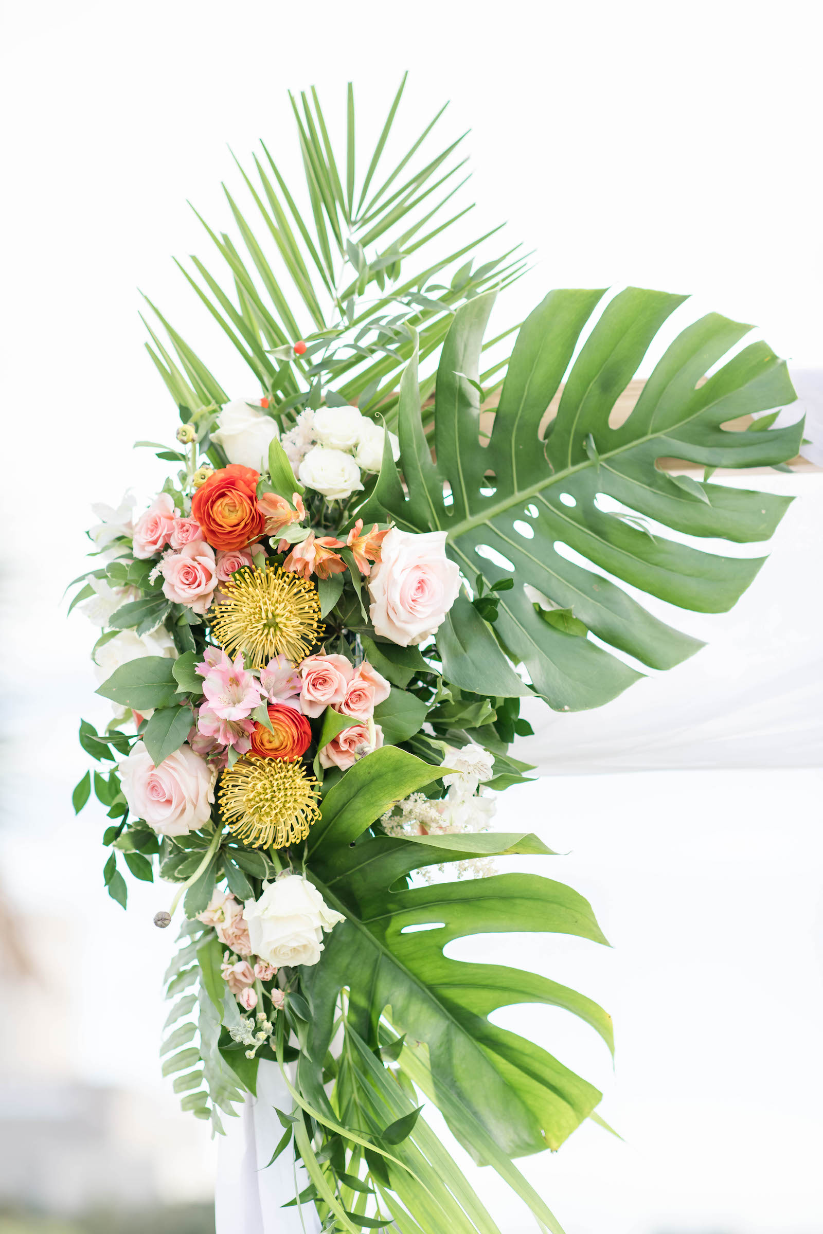 Tropical Wedding Ceremony Decor, Monstera and Palm Fronds, Pink and White Roses, Yellow Pincushion Proteas, Orange Floral Arrangement on Arch | Tampa Bay Wedding Planner Coastal Coordinating