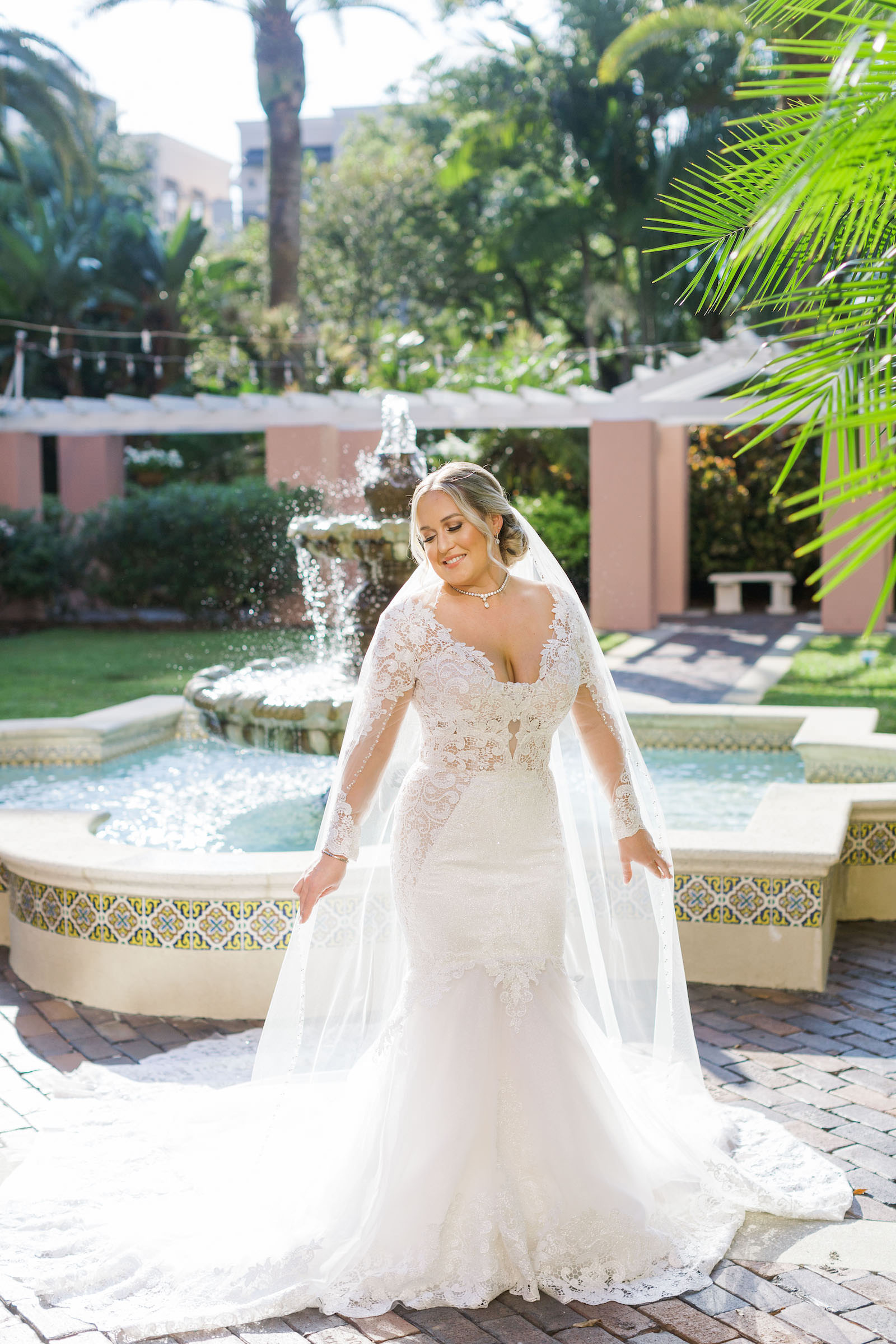 Tampa Bride Wearing Long Sleeve Lace and Illusion Plunging Neckline Wedding Dress in Front of Courtyard Water Fountain at St. Pete Vinoy Renaissance