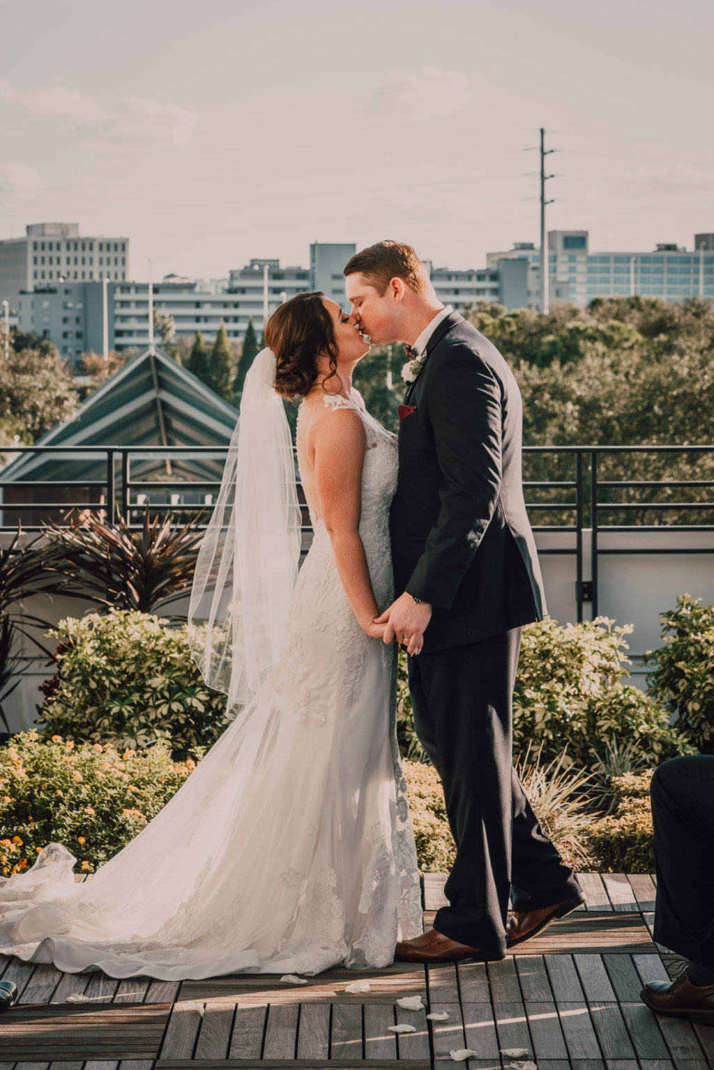 Bride and Groom First Kiss Portrait at Tampa Heights Rooftop Wedding Ceremony | Lace Sheath V Neck Illusion Sleeve Bridal Gown Wedding Dress with Sheer Embroidered Train | Groom Wearing Classic Black Suit Tux