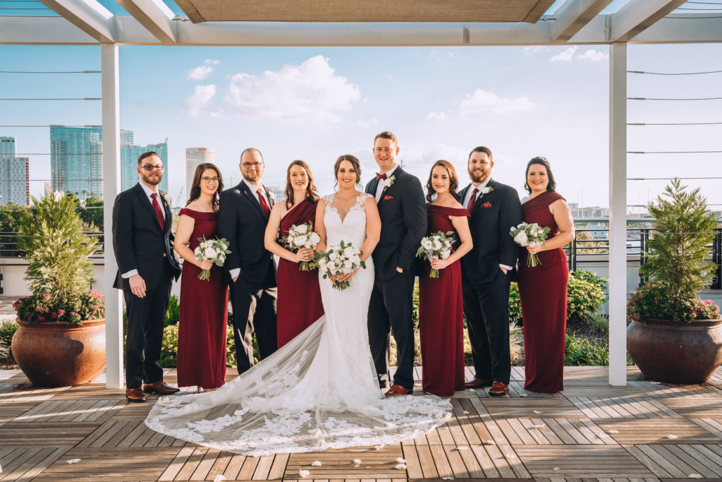 Outdoor Party Portrait at Tampa Rooftop Ceremony | Lace Sheath V Neck Illusion Sleeve Bridal Gown Wedding Dress with Sheer Embroidered Train | Simple White Rose Wedding Bouquets with Eucalyptus Greenery | Burgundy Maroon Long Bridesmaid Dresses by David's Bridal | Groom and Groomsmen Wearing Classic Black Suit Tux