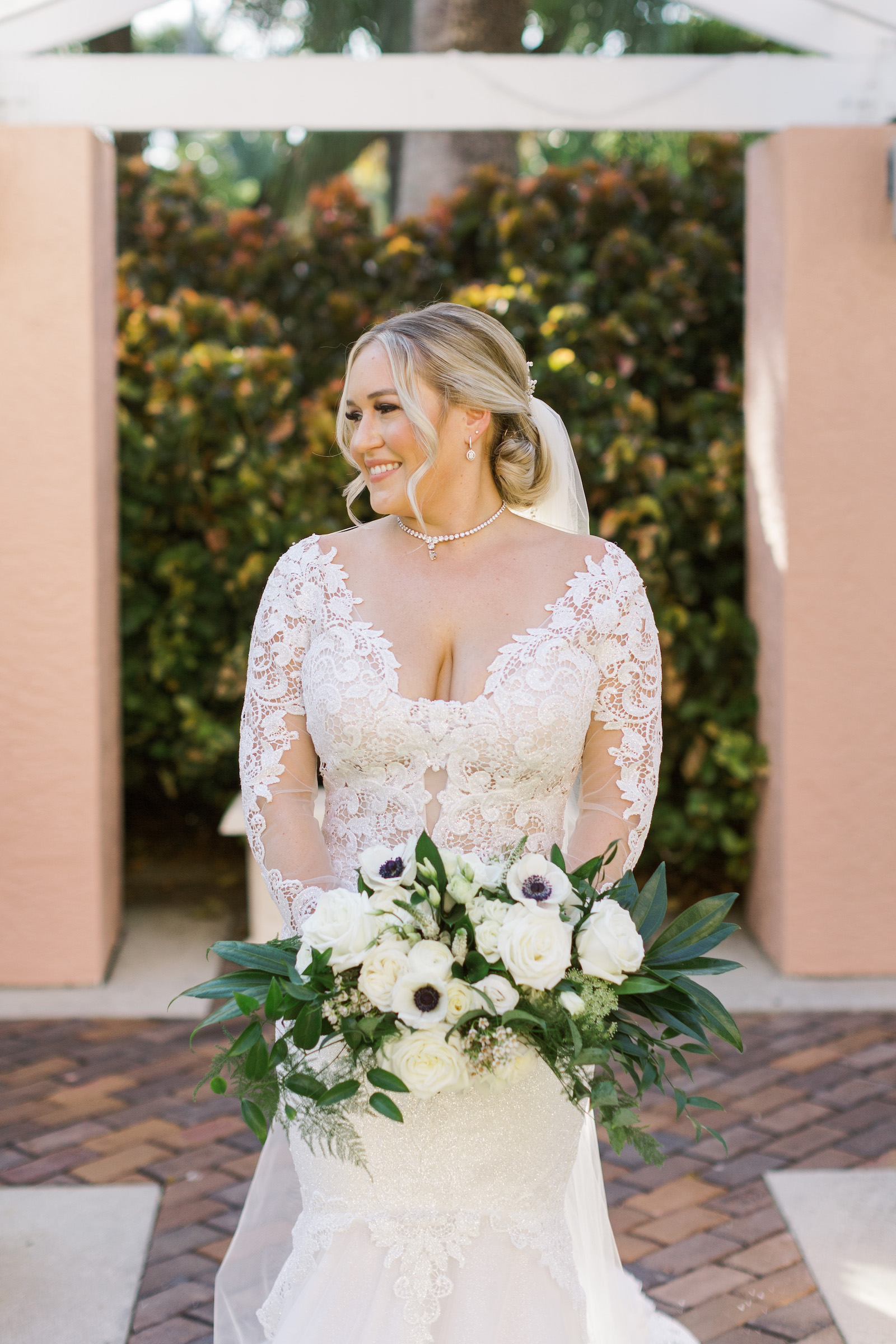 Tampa Bride Wearing Lace and Illusion Plunging Neckline Wedding Dress holding White Anemone. Rose and Greenery Floral Bouquet