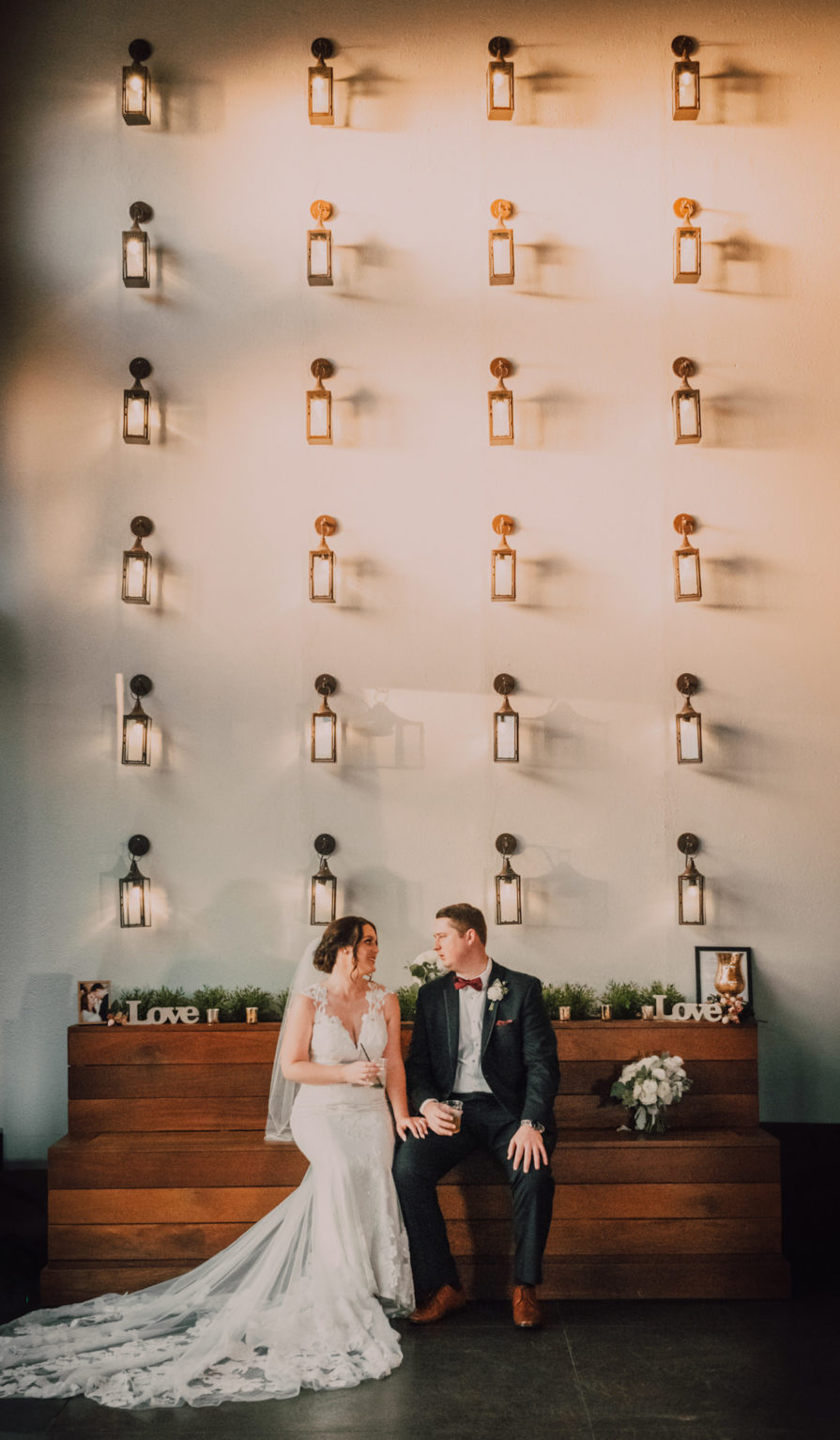 Bride and Groom Indoor Portrait in Tampa Heights CAVU with Lantern Wall Backdrop | Lace Sheath V Neck Illusion Sleeve Bridal Gown Wedding Dress with Sheer Embroidered Train | Groom Wearing Classic Black Suit Tux | UNIQUE Weddings + Events