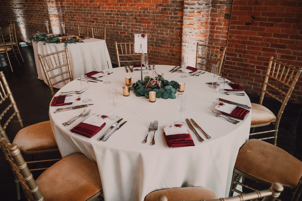 Tampa Wedding Reception Table with Gold Chiavari Chairs from Kate Ryan Event Rentals | Simple Eucalyptus Greenery with Gold Geometric Vase and Mercury Glass Candles on White Table Linen with Burgundy Napkins | UNIQUE Weddings + Events