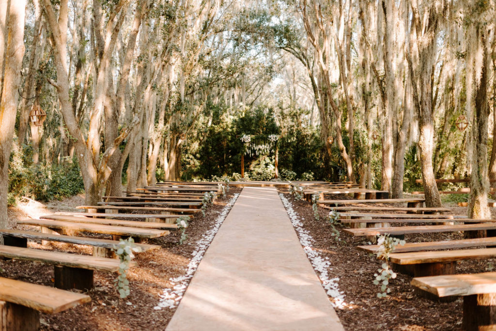 Outdoor Wedding Ceremony with Wood Benches and Wood Arch at Plant City Wedding Venue Florida Rustic Barn Weddings