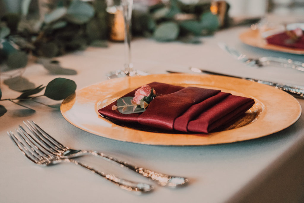 Tampa Wedding Reception Table with Gold Chargers and Eucalyptus Greenery Garland on White Table Linen with Burgundy Napkins