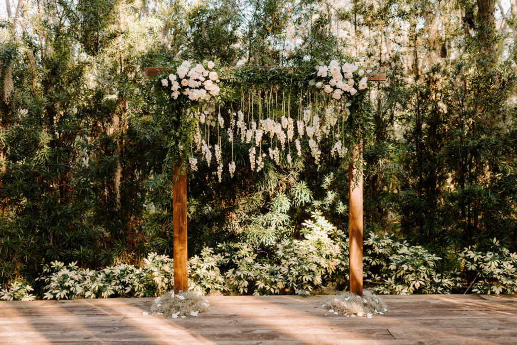 Outdoor Wedding Ceremony Backdrop wood Arch Arbor with Greenery and White Roses and Suspended Hanging Stock Flowers