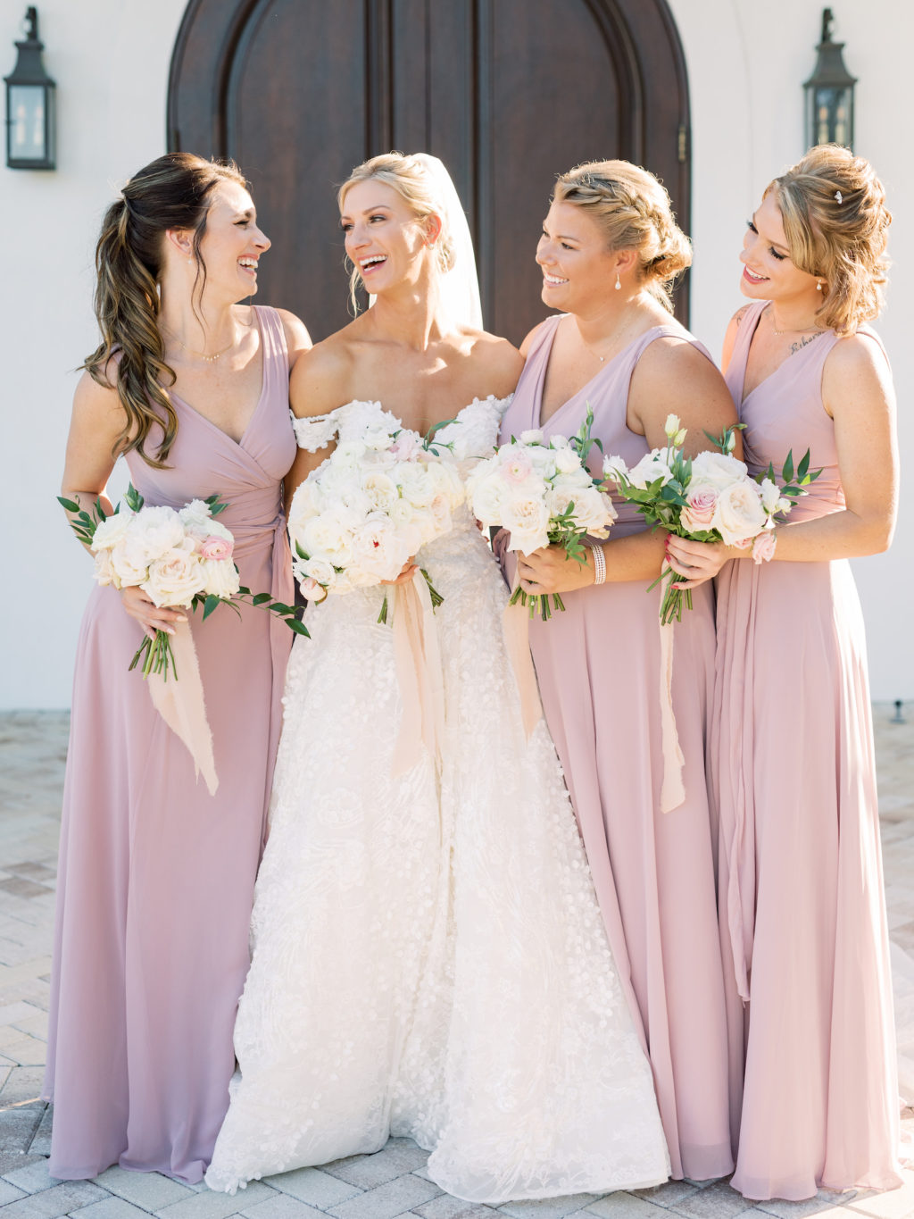 Timeless Romantic Bride Wearing Floral Lace Over Tulle Off the Shoulder Ballgown Allure Couture Bridal Wedding Dress, Bridesmaids in Mauve Matching Dresses Holding Classic Ivory and Blush Pink Roses Floral Bouquets | Tampa Bay Wedding Hair and Makeup Artist Femme Akoi Beauty Studio