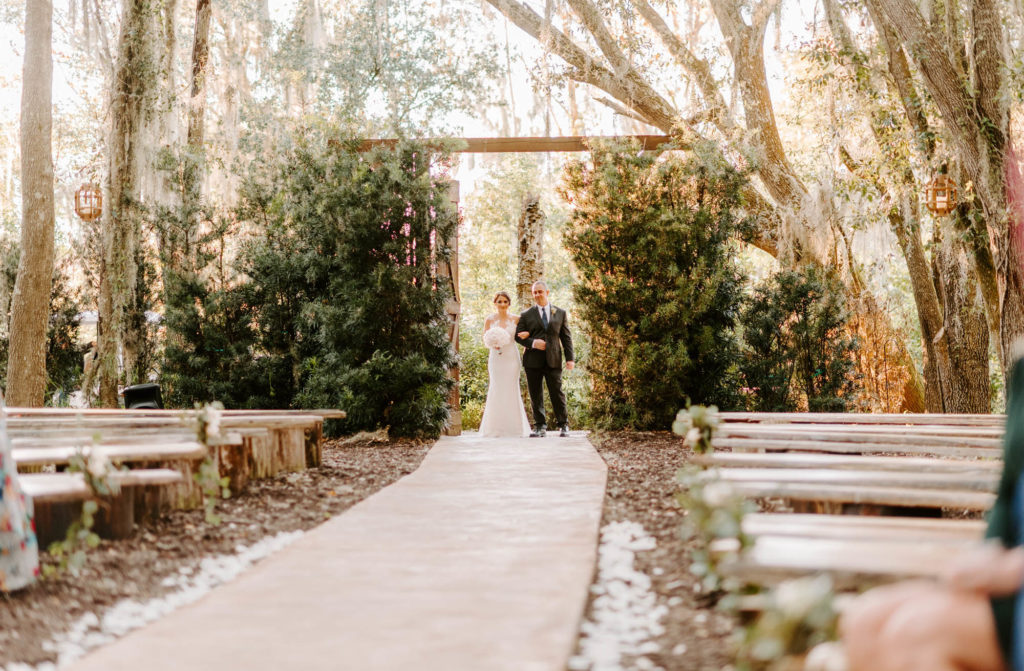 Bride Walking Down Aisle with Father during Outdoor Wedding Ceremony with Wood Benches at Plant City Wedding Venue Florida Rustic Barn Weddings