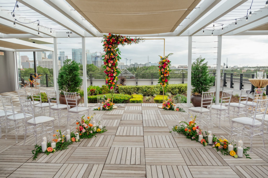Moroccan Inspired Elopement Wedding Decor, Gold Arch with Colorful Flowers, Yellow, Orange, Red and Pink Roses, Greenery, Acrylic Chiavari Chairs, Hurricane Candles and Grapefruits | Tampa Bay Wedding Planner UNIQUE Weddings + Events | Wedding Rentals Kate Ryan Event Rentals