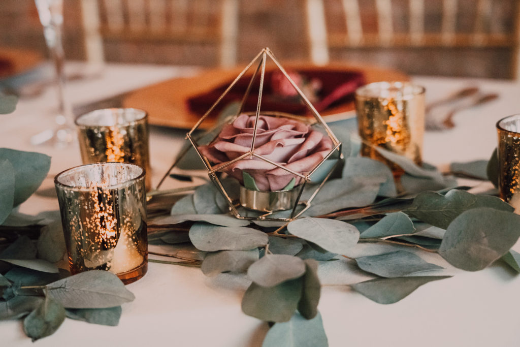 Tampa Wedding Reception Table with Simple Eucalyptus Greenery with Gold Geometric Vase and Mercury Glass Candles on White Table Linen with Burgundy Napkins