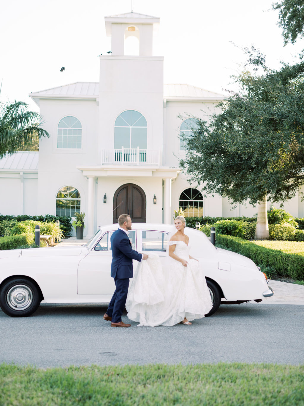 Timeless Florida Groom Holding Train of Bride's Dress in Front of White Vintage Car | Safety Harbor Traditional Wedding Ceremony Venue Harborside Chapel