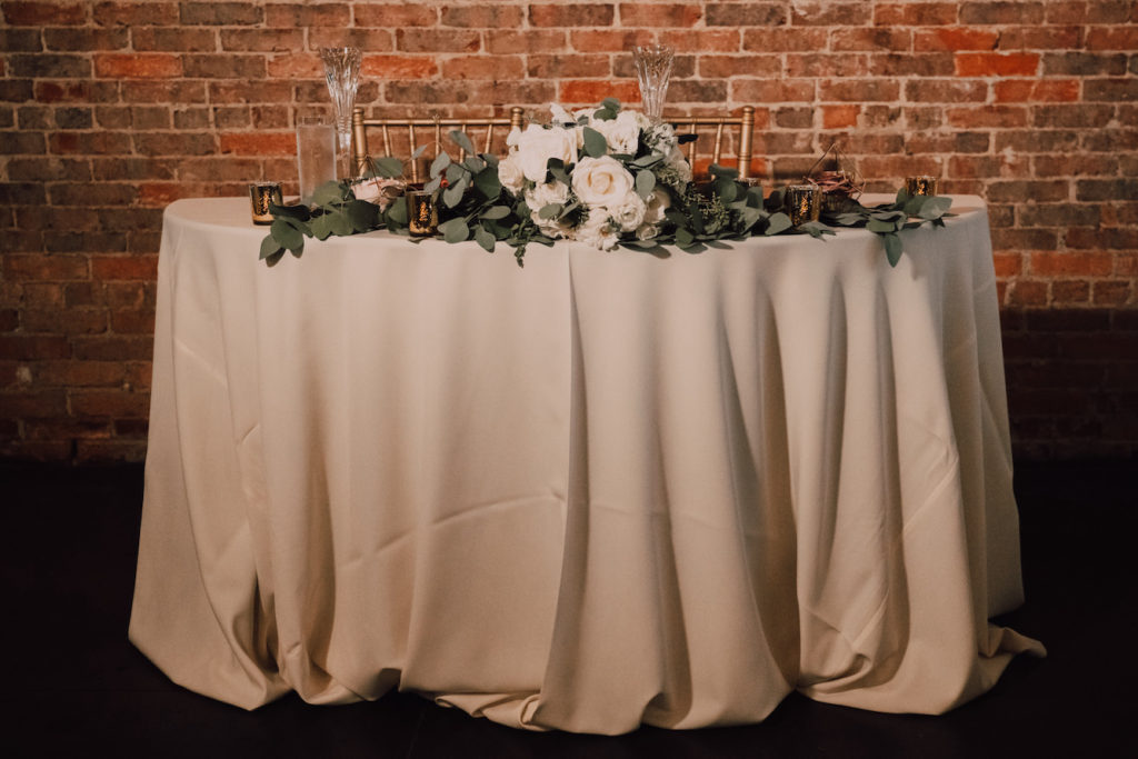 Tampa Wedding Sweetheart Table with Simple Eucalyptus Greenery Garland and Gold Mercury Glass Candles on Gold Champagne Table Linen