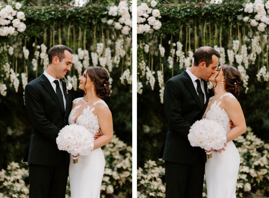 Outdoor Bride and Groom Portrait in front of Wedding Ceremony Backdrop wood Arch Arbor with Greenery and White Roses and Suspended Hanging Stock Flowers | Groom Wearing Classic Black Suit Tux | White Peony Bridal Bouquet | Sheath Illusion Lace Bridal Gown wedding Dress