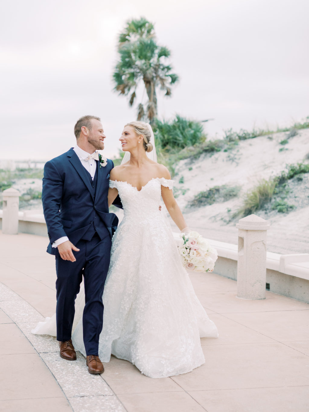 Timeless Florida Bride Wearing Floral Lace Over Tulle Off the Shoulder Allure Couture Ballgown Wedding Dress, Groom in Blue Tuxedo and Ivory Bowtie | Tampa Bay Wedding Hair and Makeup Artist Femme Akoi Beauty Studio