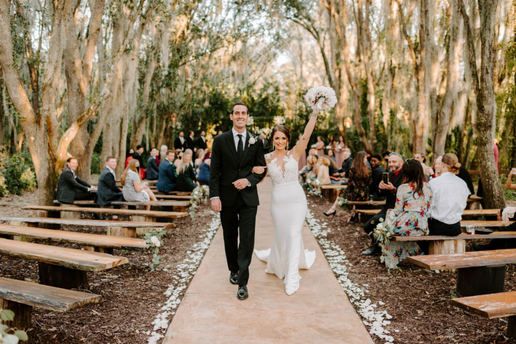 Bride and Groom Exit during Outdoor Wedding Ceremony at Plant City Wedding Venue Florida Rustic Barn Weddings | Groom Wearing Classic Black Suit Tux | White Peony Bridal Bouquet | Sheath Illusion Lace Bridal Gown wedding Dress