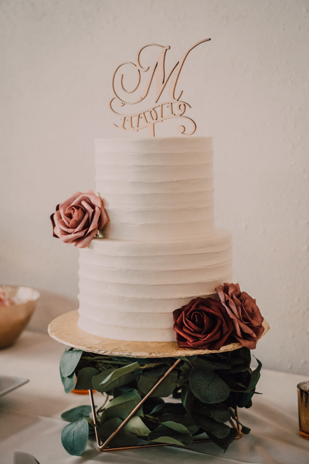Simple Two Tier Wedding Cake with Ribbed Buttercream Icing on Gold Geometric Cake Stand with Burgundy and Blush Pink Roses and Die Cut Monogram Cake Topper