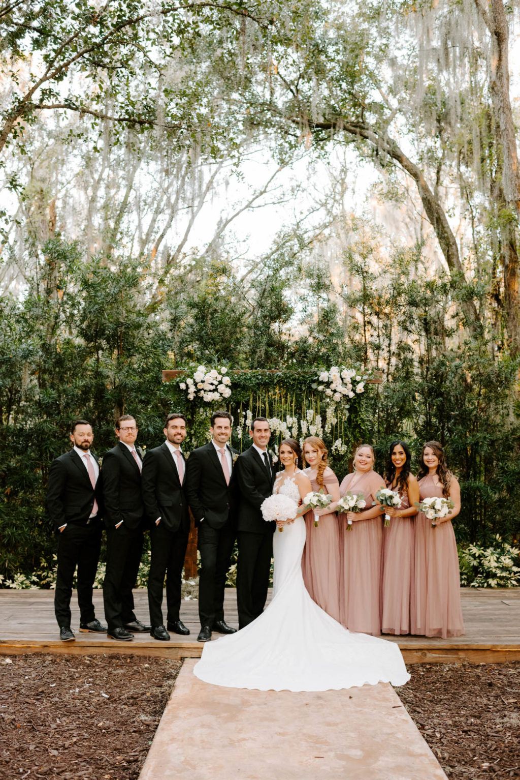 Outdoor Wedding Party Portrait in front of Wedding Ceremony Backdrop wood Arch Arbor with Greenery and White Roses and Suspended Hanging Stock Flowers | Groom and Groomsmen Wearing Classic Black Suit Tux | White Peony Bridal Bouquet | Sheath Illusion Lace Bridal Gown wedding Dress | Long Dusty Rose Mauve Pink Bridesmaid Dresses