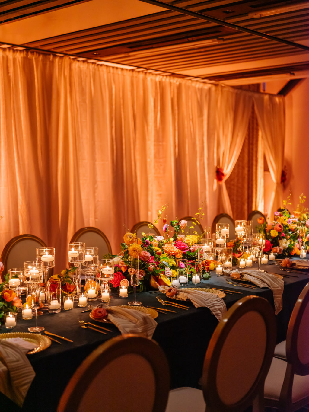 Moroccan Inspired Elopement Wedding Reception Decor, Orange Linen Drapery, Long Feasting Table with Dark Green Tablecloth, Colorful and Bright Orange, Yellow, Pink Flower Centerpieces, High Low Floating and Votive Candles, Gold Chargers and Flatware | Tampa Bay Wedding Planner UNIQUE Weddings + Events | Wedding Furniture Rentals Kate Ryan Event Rentals