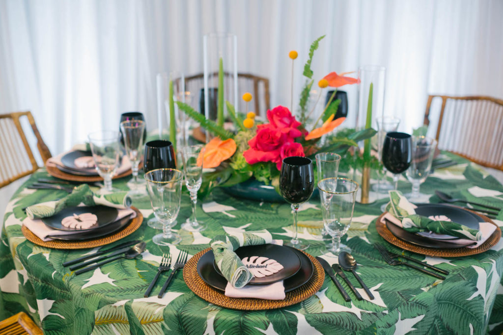 Palm Leave Linen with Wicker Charger, Black Place Setting and Dishes, and Vibrant Pink and Orange Centerpiece | Tropical Destination Beach Wedding Inspiration | Bellwether Beach Resort Styled with Love by Marry Me Tampa Bay