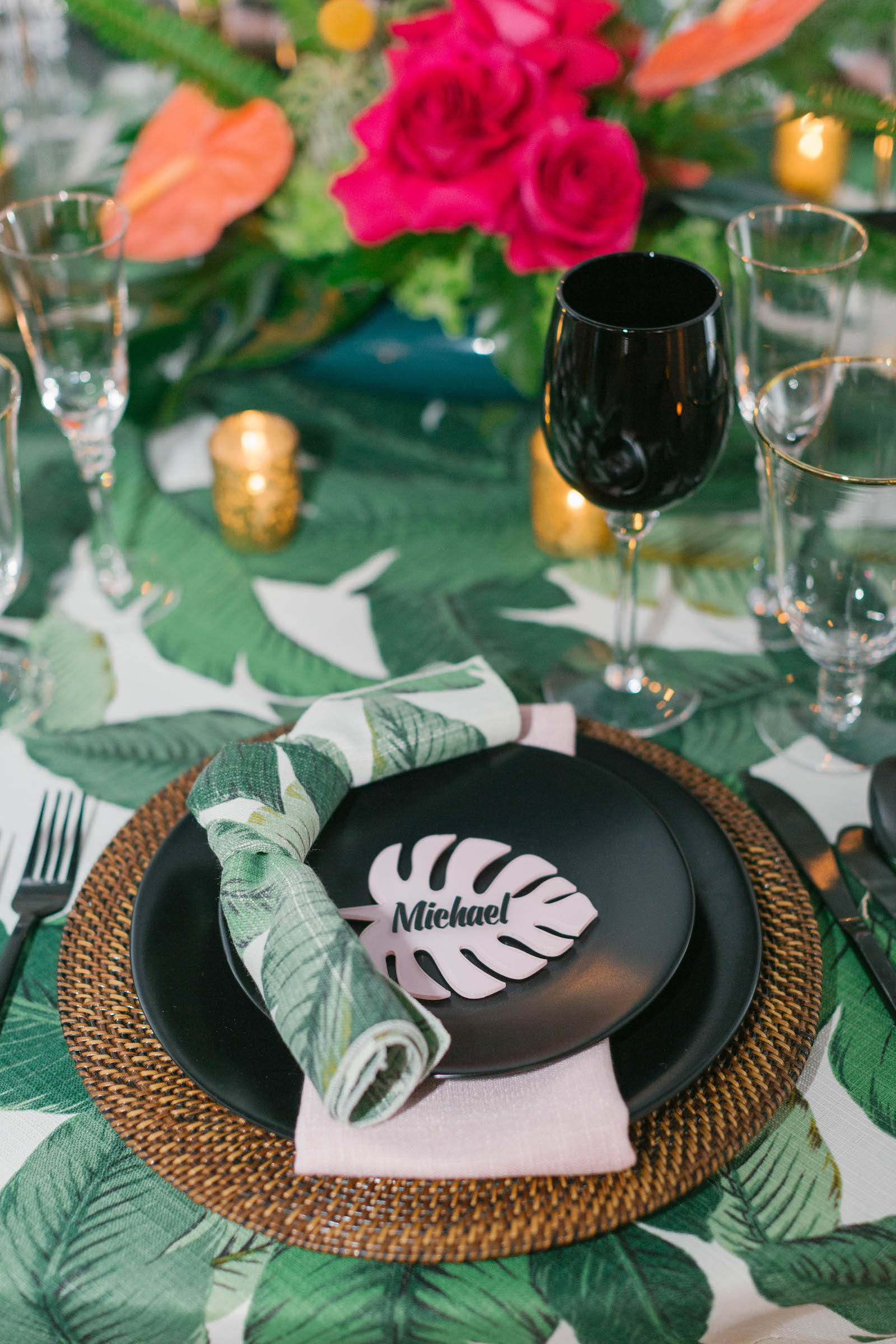 Palm Leave Linen with Wicker Charger, Black Place Setting, Palm Leaf Name Card,and Dishes, and Vibrant Pink and Orange Centerpiece   Tropical Destination Beach Wedding Inspiration   Bellwether Beach Resort Styled with Love by Marry Me Tampa Bay