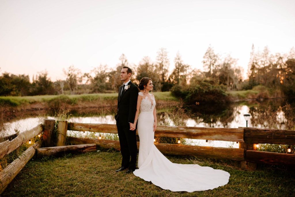 Outdoor Bride and Groom Sunset Portrait at Florida Lake | Groom Wearing Classic Black Suit Tux | White Peony Bridal Bouquet | Sheath Illusion Lace Bridal Gown wedding Dress