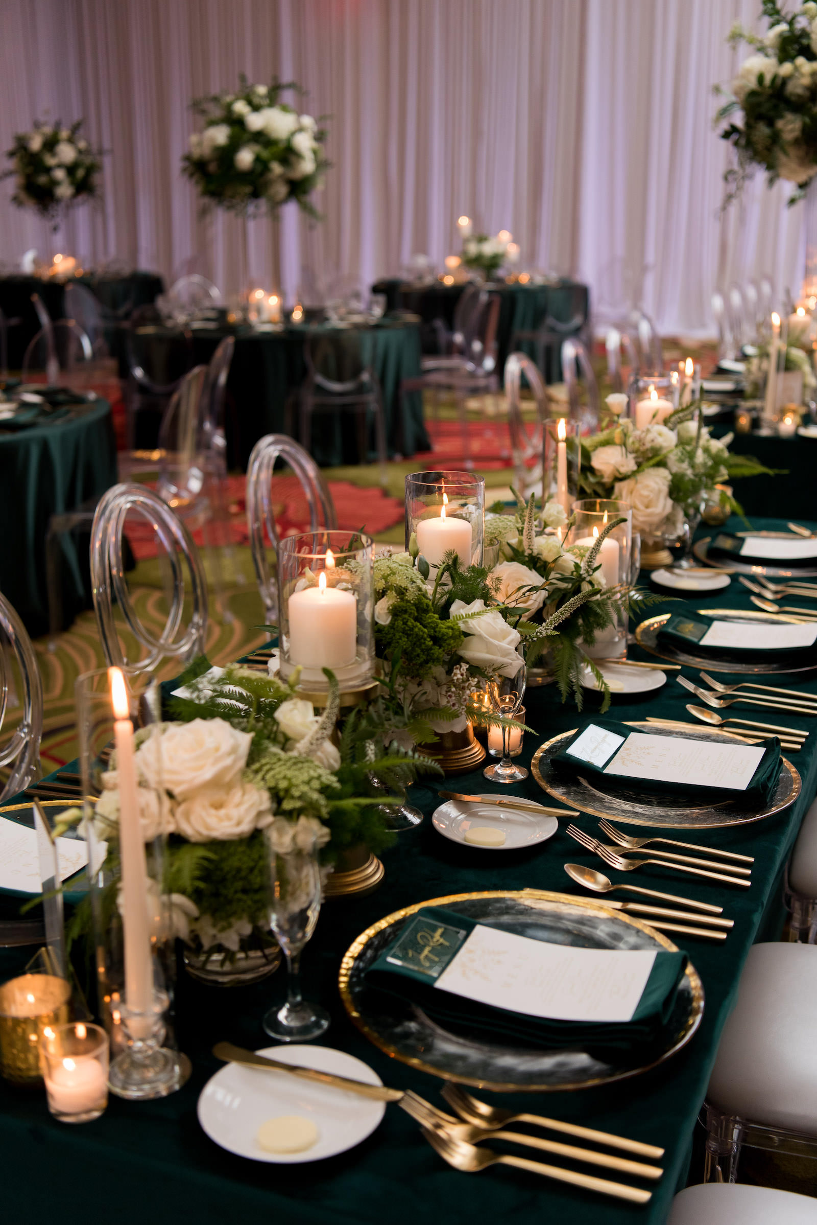Elegant Wedding Reception Decor, Long Feasting Table with Emerald Green Linens, Gold Rimmed Chargers and Flatware Candles, Low White Roses and Greenery Floral Arrangements, Acrylic Chiavari Chairs | Tampa Bay Wedding Planner Parties A'la Carte | Wedding Chairs, Chargers, Chairs and Flatware Rentals A Chair Affair | Wedding Florist Bruce Wayne Florals