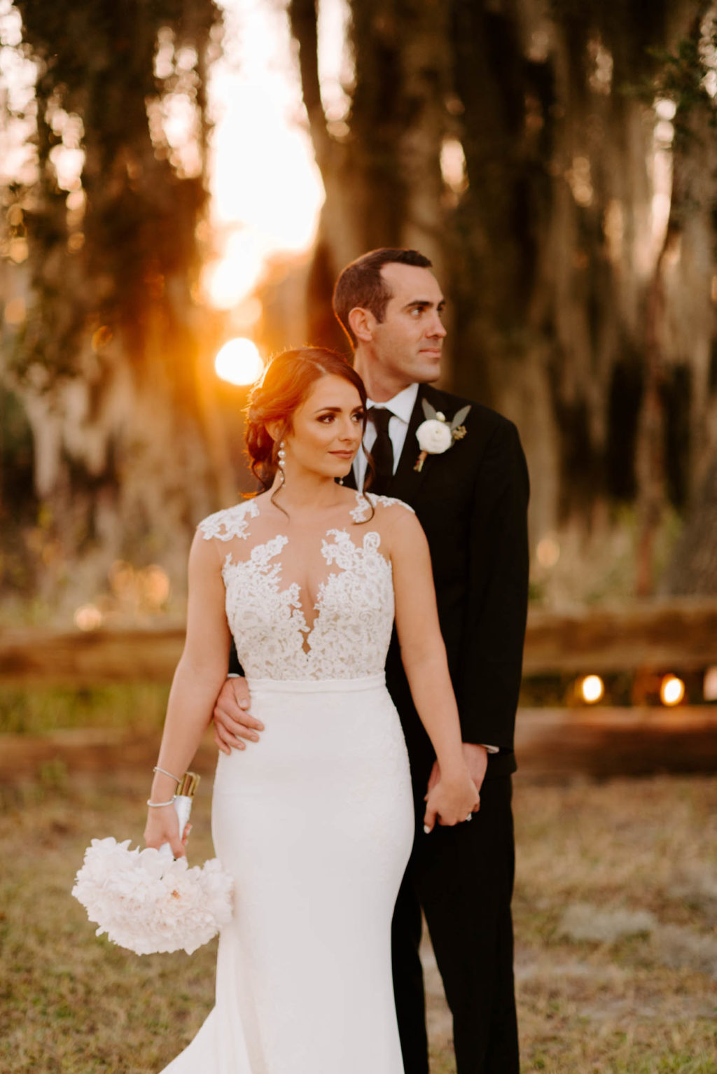 Outdoor Bride and Groom Sunset Portrait | Groom Wearing Classic Black Suit Tux | White Peony Bridal Bouquet | Sheath Illusion Lace Bridal Gown wedding Dress
