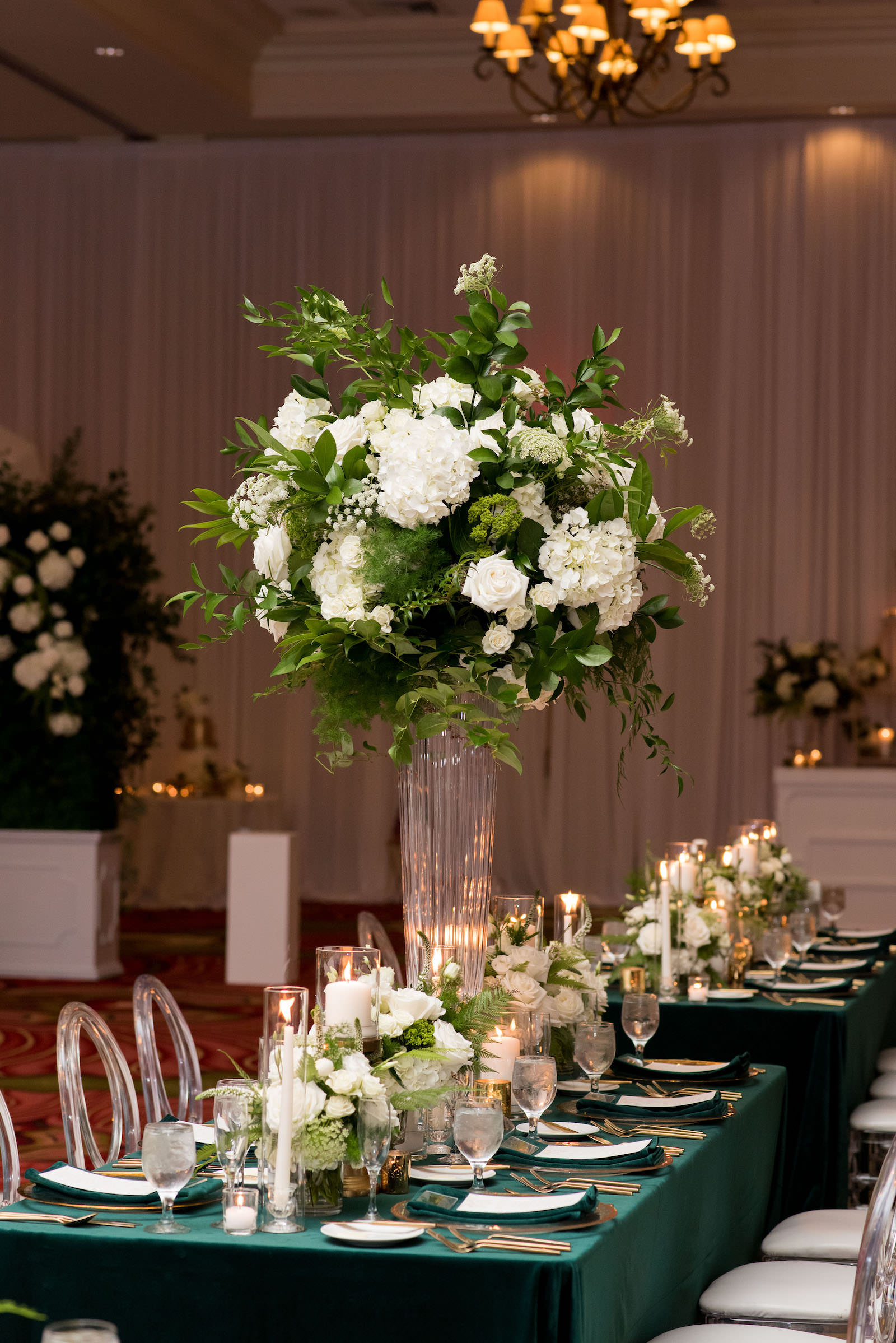 Elegant Wedding Reception Decor, Long Feasting Table with Emerald Green Linens, Gold Rimmed Chargers and Flatware Candles, Tall White Roses and Greenery Floral Arrangements, Acrylic Chiavari Chairs | Tampa Bay Wedding Planner Parties A'la Carte | Wedding Chairs, Chargers, Chairs and Flatware Rentals A Chair Affair | Wedding Florist Bruce Wayne Florals