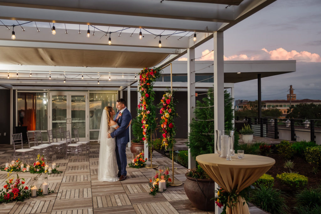 Florida Bride and Groom Outside Tampa Bay Wedding Venue Rooftop 220 at Armature Works, Gold Arch with Colorful Moroccan Inspired Lush Flower Arrangements, Yellow, Pink Fuschia, Orange Roses and Greenery | Wedding Planner UNIQUE Weddings + Events | Wedding Rentals Kate Ryan Event Rentals