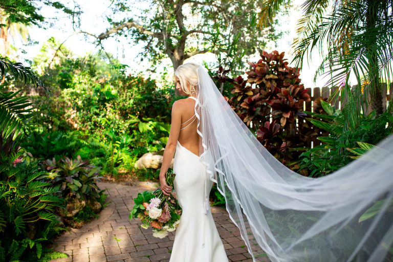 Florida Bride in White Mermaid Silhouette Wedding Dress, Open Back, Long Cathedral Veil Blowing in the wind at Sarasota Garden Club, Bride Holding Citrus Inspired Bouquet with light pink, orange, and yellow flowers