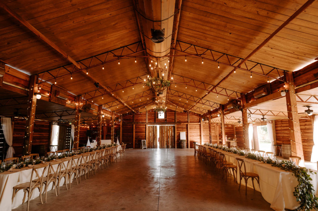 Wood Barn Reception at Plant City Wedding Venue Florida Rustic Barn Weddings | Long Feasting Tables with White Linens and Eucalyptus Greenery Garland Centerpieces and Wood Cross Back Chairs under a Canopy of String Lights