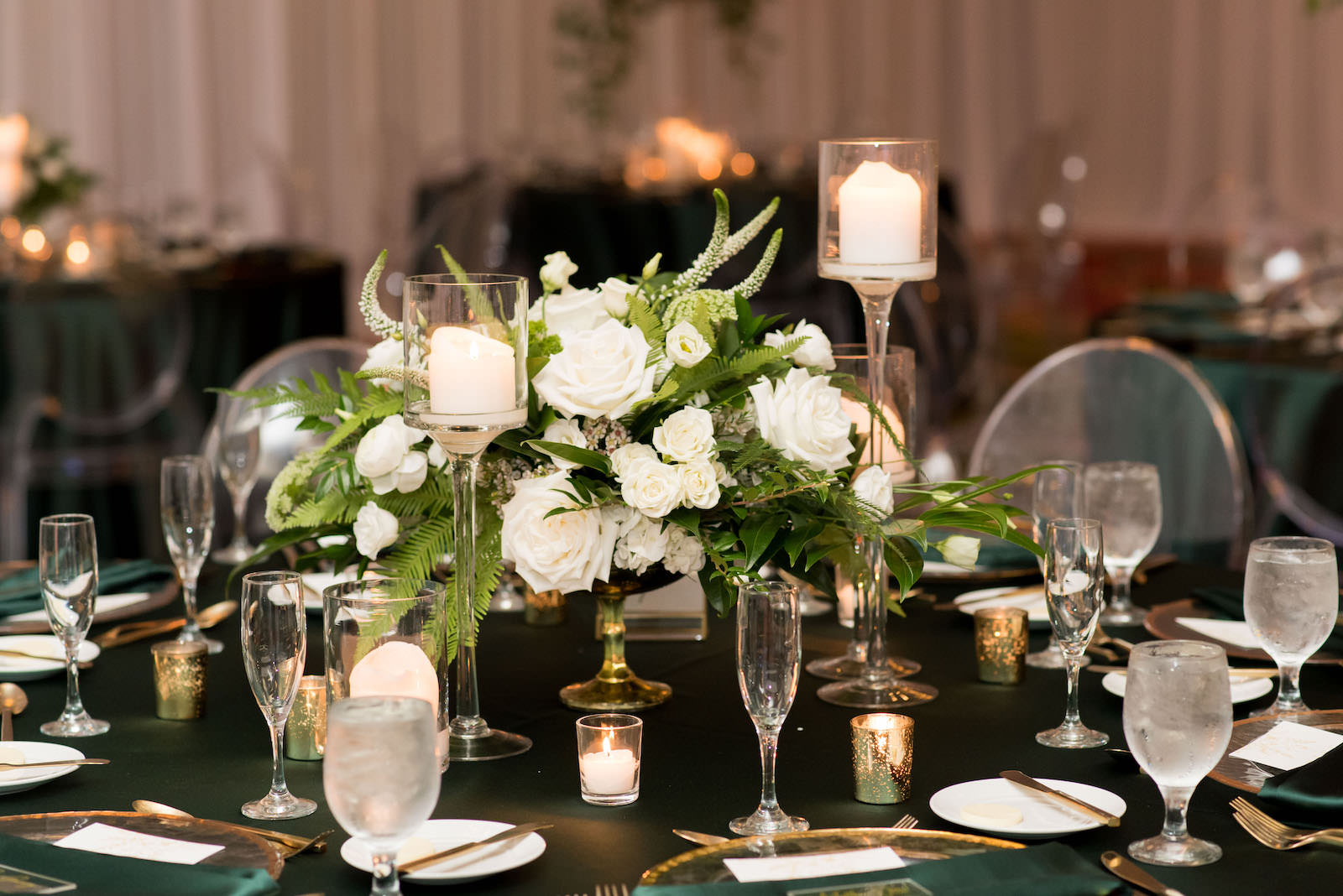 Elegant Wedding Reception Decor, Table with Emerald Green Linens, Gold Rimmed Chargers and Flatware Candles, Low White Roses and Greenery Floral Arrangements, Acrylic Chiavari Chairs | Tampa Bay Wedding Planner Parties A'la Carte | Wedding Chairs, Chargers, Chairs and Flatware Rentals A Chair Affair | Wedding Florist Bruce Wayne Florals