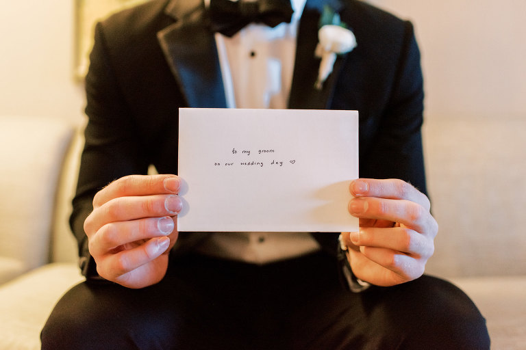 Groom Holding Note From Bride on Wedding Day Portrait in Tuxedo