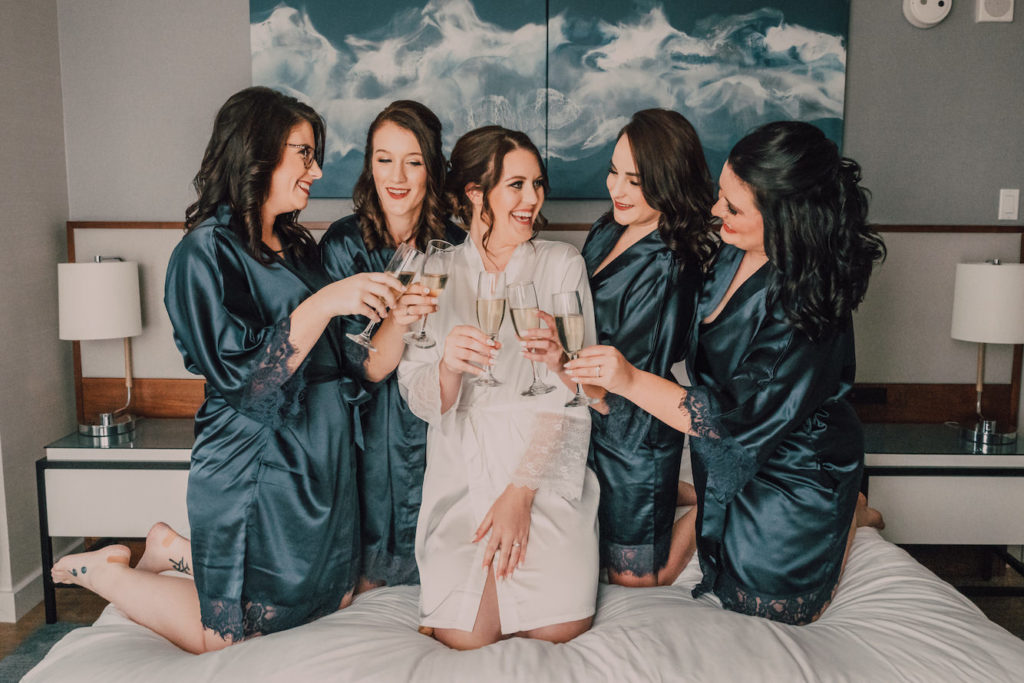 Bride and Bridesmaids Getting Ready in Navy Blu Silk Robes and Toasting with Glasses of Bubbly Champagne | Bonnie Newman Creative