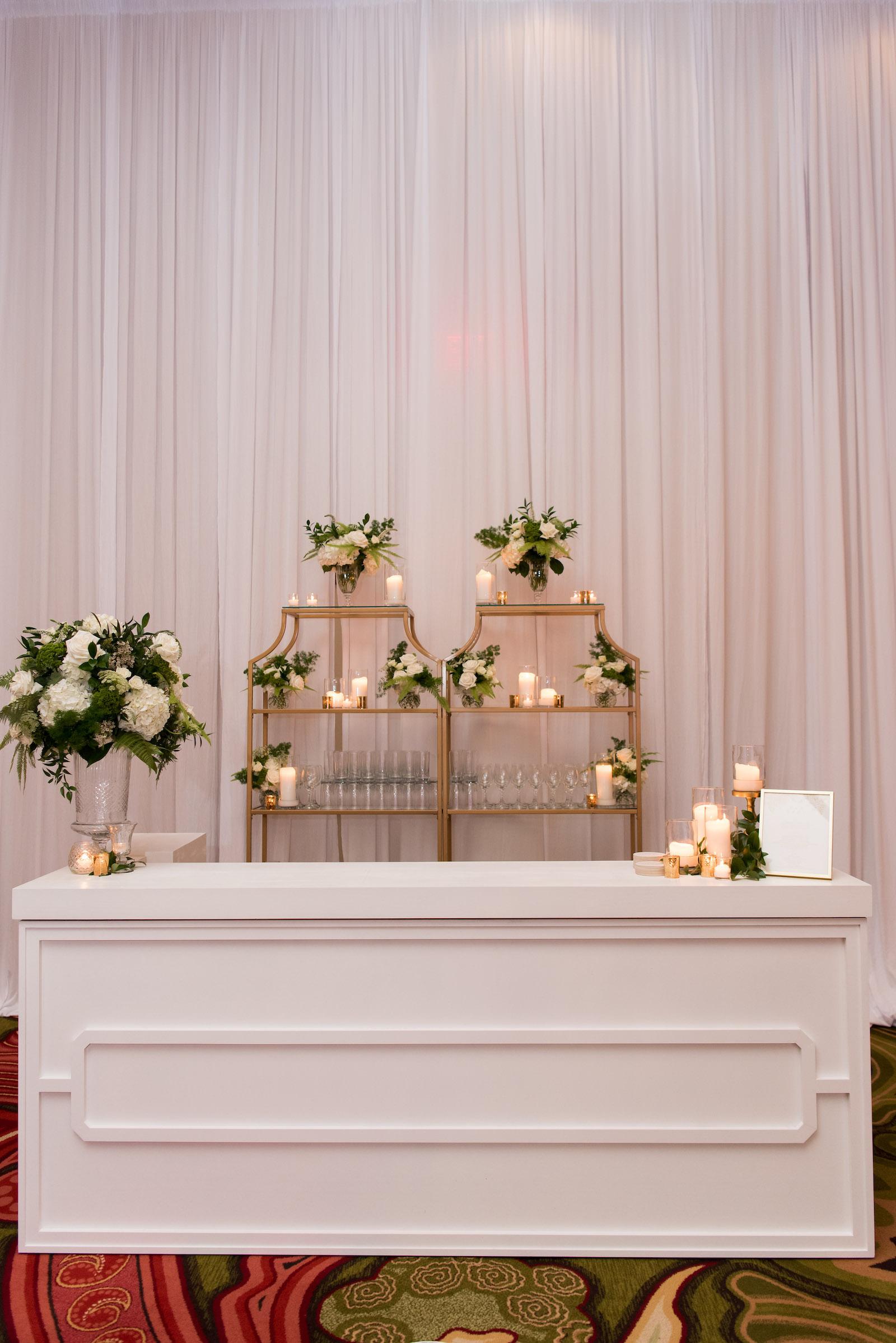 Elegant Wedding Reception Decor, White Bar, Gold Shelves with Greenery and White Florals | Tampa Bay Wedding Planner Parties A'la Carte | St Pete Wedding Venue The Vinoy | Wedding Rentals A Chair Affair | Wedding Florist Bruce Wayne Florals